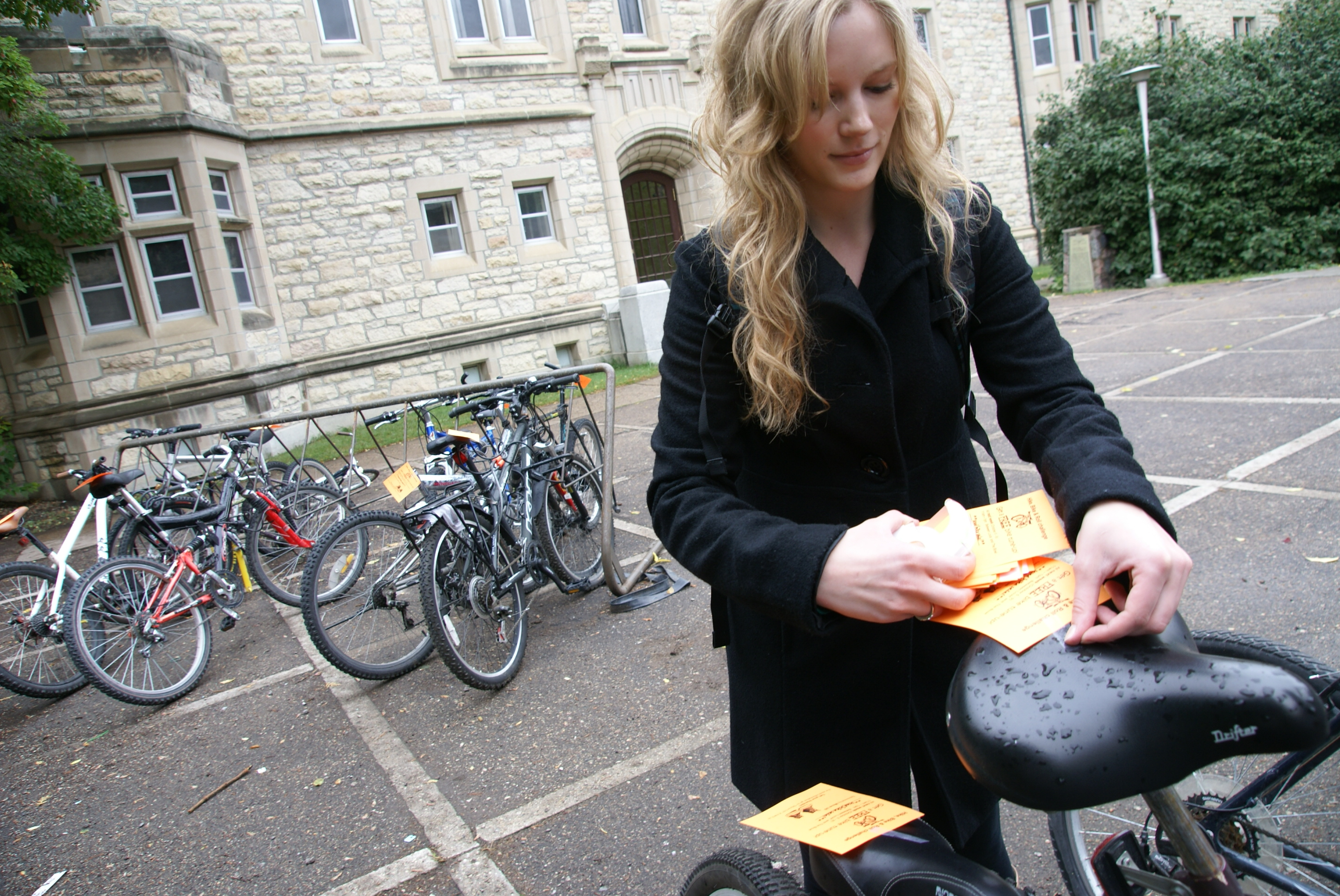 A Green Pack volunteer handing out bike notices on campus