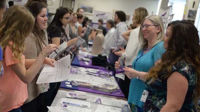 A picture of people meeting each other at a career fair.