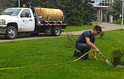A groundskeeper at the U of S irrigating flower beds with collected rainwater
